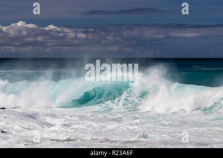 Ola curling en hawaiano Kona, cerca de la playa. Spray de volar de regreso en la parte superior de la onda. Espuma de oleada anterior en primer plano. Mar Blanco spray lanzados al aire.