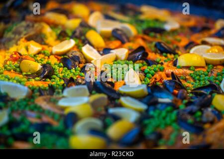 Spanish paella de mariscos con pollo, mejillones, gambas, camarones y chorizo salchichas en pan tradicional de cerca en un mercado de alimentación