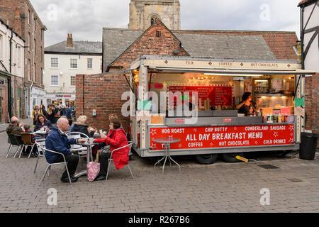 Clientes sentarse en las mesas, comer alimentos en la calle y bebiendo y 2 mujeres trabajan en Newgate asado de cerdo van - Ruinas del mercado, York, Yorkshire, Inglaterra, Reino Unido. Foto de stock