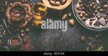 Fondo de chocolate con diferentes nueces, especias, cacao en polvo y las bebidas espirituosas, vista superior. Repostería casera con pralines, trufas ingredientes. Bro