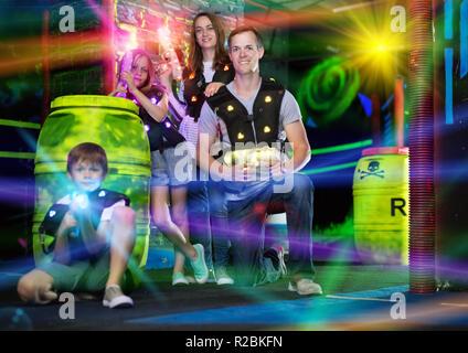 Retrato de niños felices y sus padres con pistolas láser en haces de color durante el juego de etiquetas láser en una habitación oscura Foto de stock