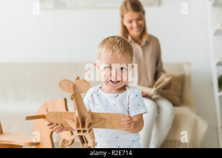 Niño feliz jugando con el avión de juguete de madera de juguete en la sala de párvulos con la madre sobre los antecedentes Foto de stock