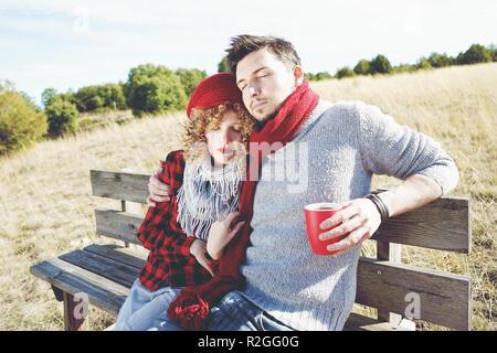 Una pareja de jóvenes felices los millennials en el amor el sol en un banco de madera y tomando una taza de café o té mientras están abrazando con la retroiluminación f Foto de stock