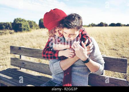Una pareja de jóvenes felices los millennials en amor, tomar el sol y sentado en un banco de madera en el campo amarillo mientras están abrazando con la retroiluminación de au Foto de stock