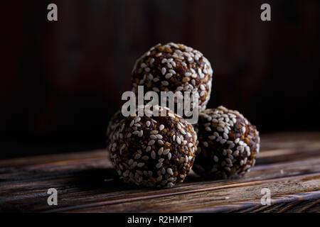 Mordeduras vegetariana orgánica saludable de energía con frutos secos, dátiles, miel y sésamo sobre un fondo de madera oscura.