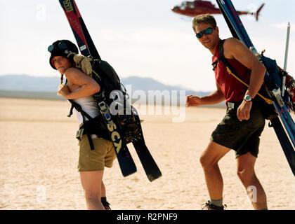Retrato de una pareja de jóvenes aventureros llevar equipamiento deportivo sobre su espalda mientras camina a través de un desierto.