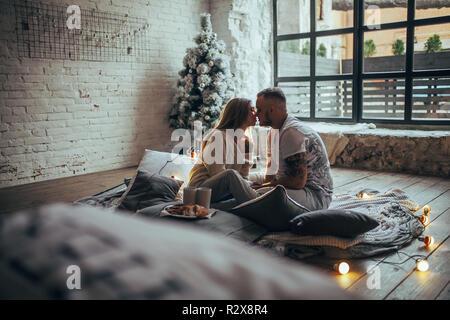 Pareja joven en el amor está sentado en el piso y besar junto a dos tazas y placa con cookies sobre fondo de árbol de Navidad bombillas incandescentes, bric