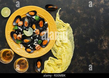 Pasta negra espaguetis con mejillones, vieiras y vino blanco sobre un fondo rústico. La comida mediterránea. Vista superior, espacio de copia