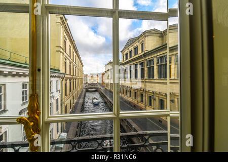 Un barco se desliza hacia abajo el invierno Kanavka Zimnyaya Canal y el río Neva en San Petersburgo, Rusia, vista desde una ventana de la galería en el interior de la Ermita
