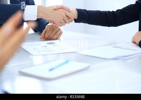 Grupo de empresarios o abogados, un apretón de manos, terminando una reunión , cerca. El éxito en la negociación y conceptos de handshake