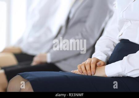 Gente de negocios esperando para entrevistas de trabajo o tomar parte en la conferencia en la oficina, cerca. Las mujeres sentadas en sillas como en cola o reunión Foto de stock