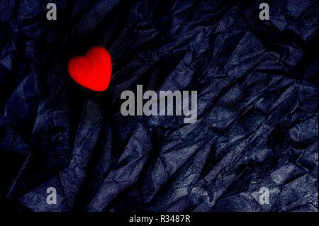Vista superior corazón rojo sobre fondo negro de textura arrugada. Feliz Día de San Valentín y el concepto de amor. Tarjeta romántica, Banner Concepto de diseño gráfico.