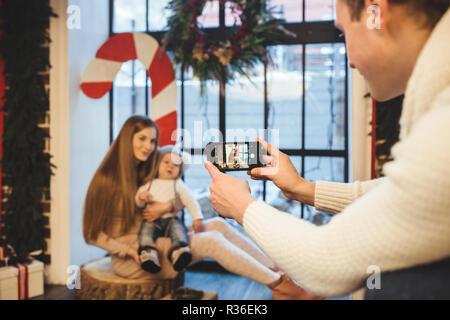 Tema fotografía móvil, amateur foto y vídeo en el teléfono. Manos Caucasian hombre sostiene utiliza smartphone realiza foto de madre e hijo en casa cerca de formul