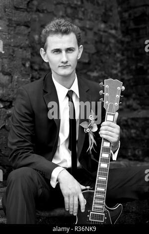 Joven apuesto novio sentado y sosteniendo una guitarra vintage, fotografía en blanco y negro