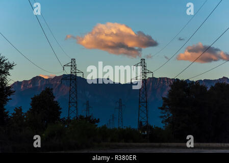Las líneas eléctricas al atardecer con montañas en segundo plano.