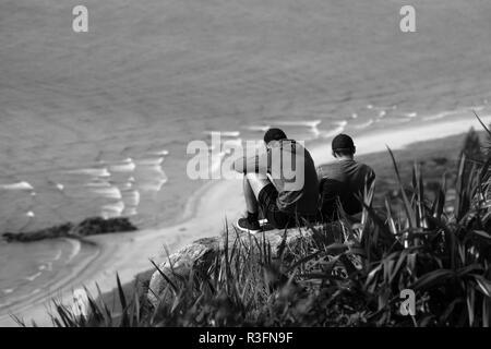 Dos amigos sentados en la cima de una montaña con vistas al océano en el Monte Maunganui, Nueva Zelanda