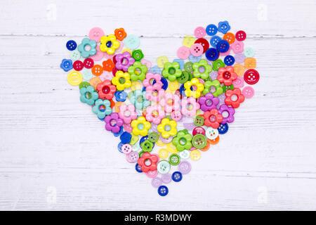 Una colección de coloridos cosiendo botones y cuentas sobre un fondo de madera pintada de blanco