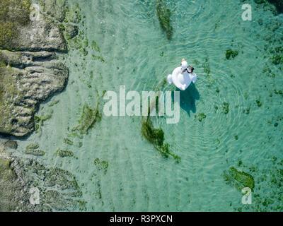 Indonesia, Bali, vista aérea del Karma Kandara beach, una mujer airbed flotando sobre el agua