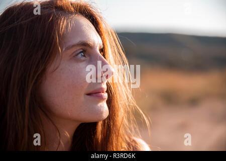 Mujer sonriente con pecas mirando lejos