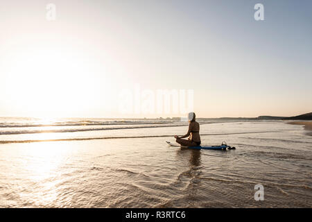 Mujer joven practicando yoga en la playa, sentado sobre la tabla de surf, meditando