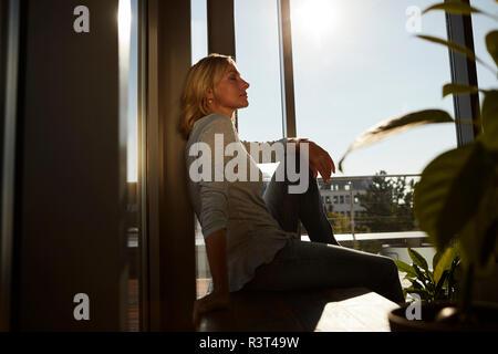 Mujer madura relajado sentado en la luz solar en casa