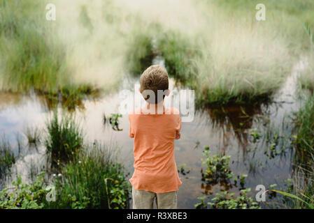 Niño desde atrás mirando las tranquilas aguas de un lago