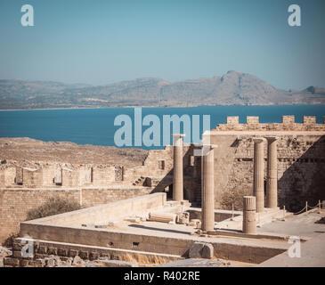 Foto horizontal con varios pilares de la Acrópolis de Lindos. Acropolys es en la isla de Rodas en el Mar Mediterráneo. El mar y el cielo es azul. Algunas rocas y hill