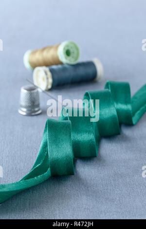 El sesgo de satén verde encuadernado con dedal y hilos de algodón
