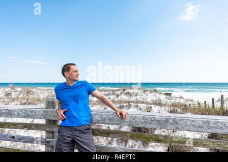 Destin, USA Miramar Beach Village ciudad día en Florida en el Golfo de México el agua del océano, el joven hombre feliz con camisa azul recostada sobre la valla de madera