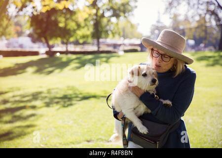 Una mujer madura besar a un perro en el parque