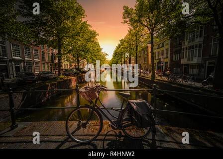 Escena icónica de Ámsterdam con la bicicleta aparcada en un puente sobre un canal de aguas tranquilas, Países Bajos