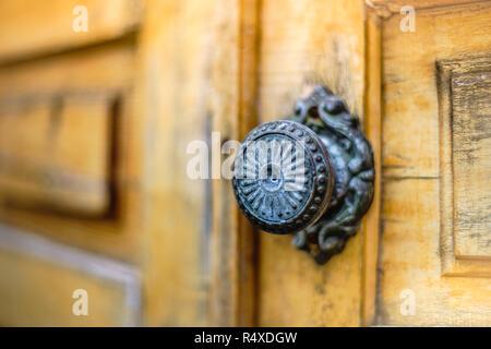 Puerta de madera antigua con un pomo de hierro redondo, de cerca