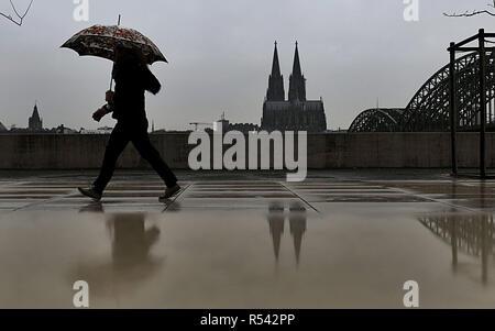 Dpatop - 29 de noviembre de 2018, Renania del Norte-Westfalia, Köln: Una mujer camina con su paraguas en la lluvia a lo largo de las orillas del Rin. - Detalle de imagen alternativo - Foto: Oliver Berg/dpa