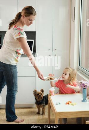 Una madre dar a su hija una merienda. Foto de stock