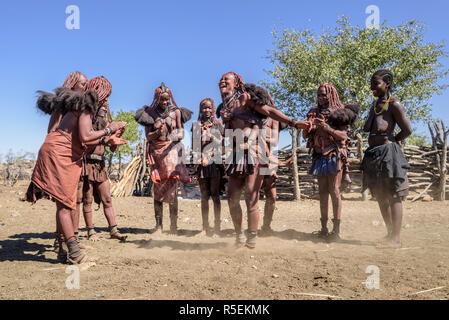Grupo de Himba las mujeres con vestidos tradicionales bailando en un círculo, algunos de ellos mientras llevan a sus bebés en sus espaldas.