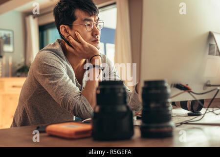 Fotógrafo macho mirando de monitor de ordenador y pensar durante la edición de fotos después de una sesión de fotos. Photo Editor trabaja en su estudio.