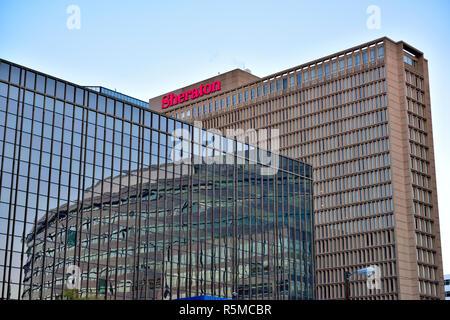 Es un edificio alto, el Sheraton Denver Downtown con reflejos en windows