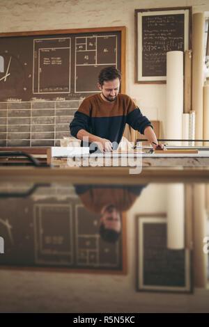 Carpintero trabajando cuidadosamente en madera en su estudio del proyecto