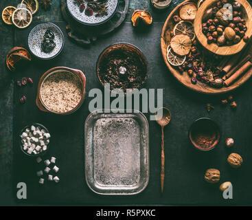 Preparación casera de vegan chocolate truffle praliné con frutos secos y nueces, mezcle los ingredientes en un fondo oscuro, vista superior. Dulces sanos. Ene