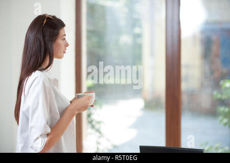 Vista lateral de la hermosa joven de ensueño de pie y mirando a la ventana. Pretty girl vistiendo en gafas y camisa blanca con cabello castaño. Modelo posando y sosteniendo una taza de café.