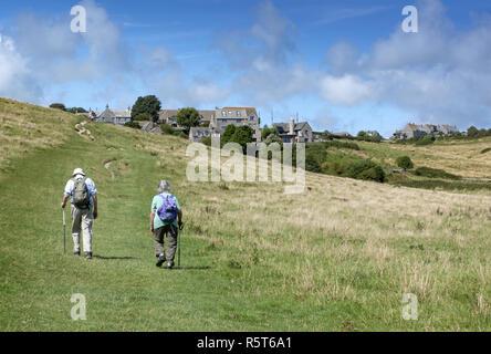 Pareja de ancianos con mochilas caminando hacia el pintoresco pueblo de Worth Matravers en la Isla de Purbeck, Dorset, Inglaterra, Reino Unido