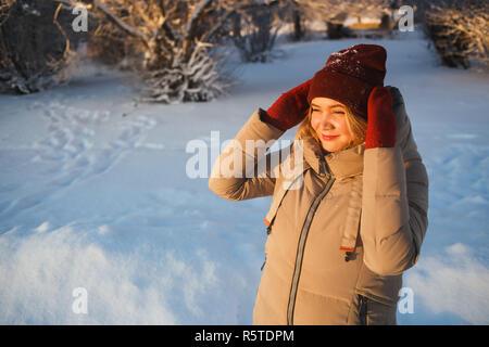 Guapa joven mujer caucásica en rojo mitones y sombrero de invierno rojo disfrutando de un buen día de sol del invierno con nieve natural. Ella sostiene su sombrero y mirando al sol. El buen humor, el clima, y el concepto de amor de invierno.