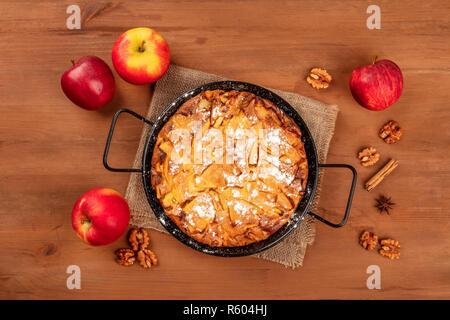 Un pastel de manzana en una sartén, tomada desde la parte superior sobre un fondo rústico de madera oscura con manzanas, nueces, canela, anís y copie el espacio Foto de stock