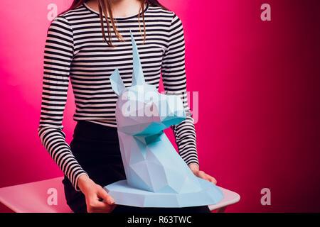 Chico de moda. Colección del diseñador. Grande Blanco Unicorn origami hechas de papel. Chica en el hermoso vestido rosado. Foto de estudio.