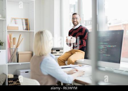 Oficina alegre hombre bebiendo café mientras hablaba con coder