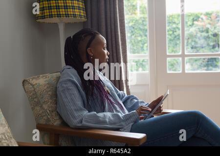 Mujer pensativa utilizando digital comprimido en una habitación liviing Foto de stock