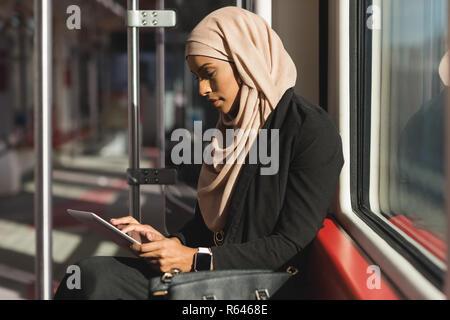 Mujer con tableta digital mientras viaja en tren Foto de stock