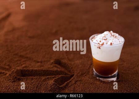 Poco taza de piccolo latte macchiato sobre una mesa cubierta con una flecha sobre el café molido como fondo