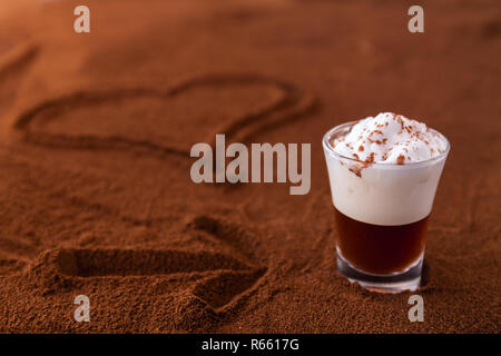 Poco taza de piccolo latte macchiato sobre una mesa cubierta con el corazón y la flecha sobre el café molido como fondo