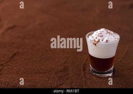 Poco taza de piccolo latte macchiato sobre una mesa cubierta con café molido como fondo
